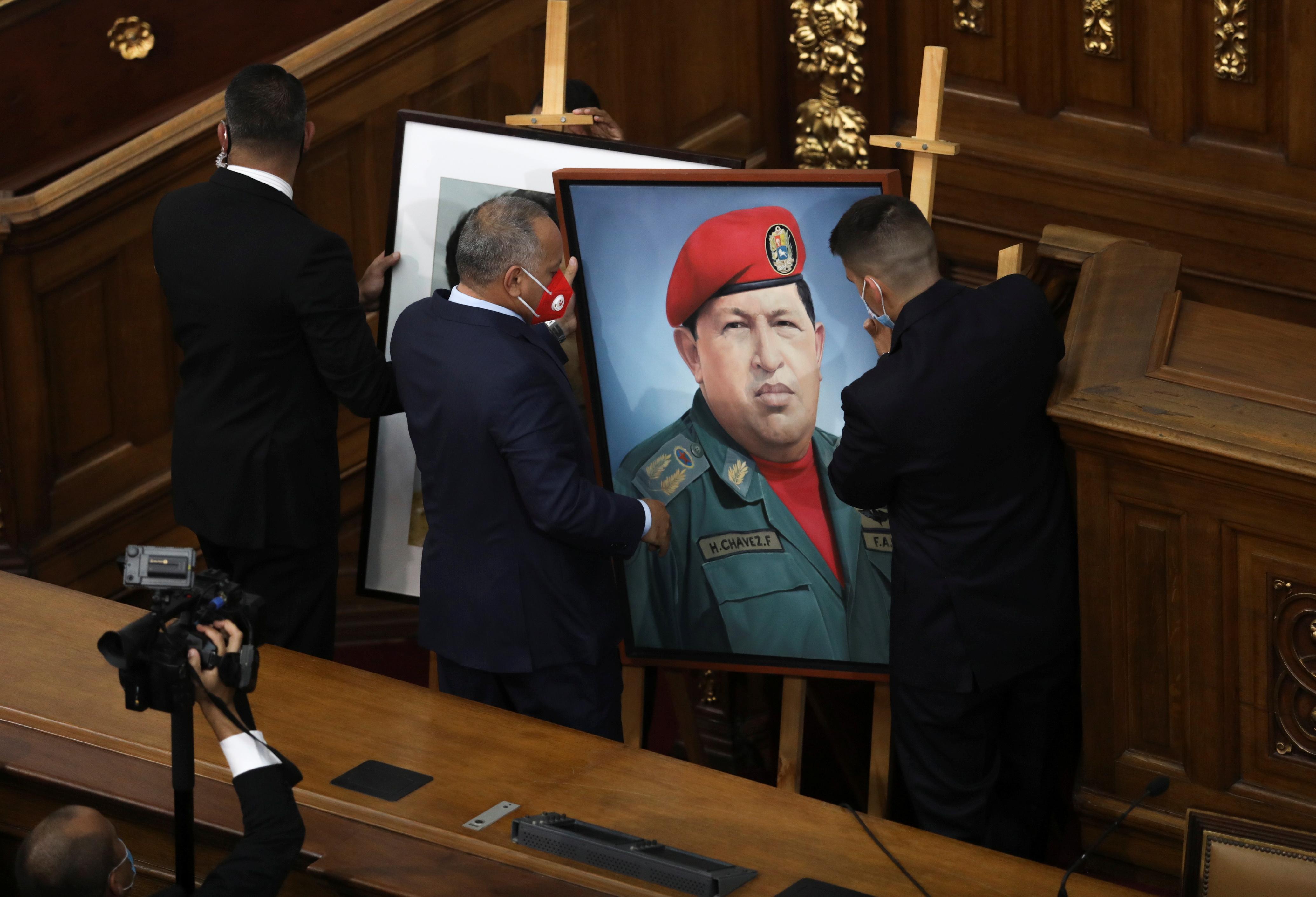 Diosdado Cabello coloca un retrato de Hugo Chávez en el Parlamento.