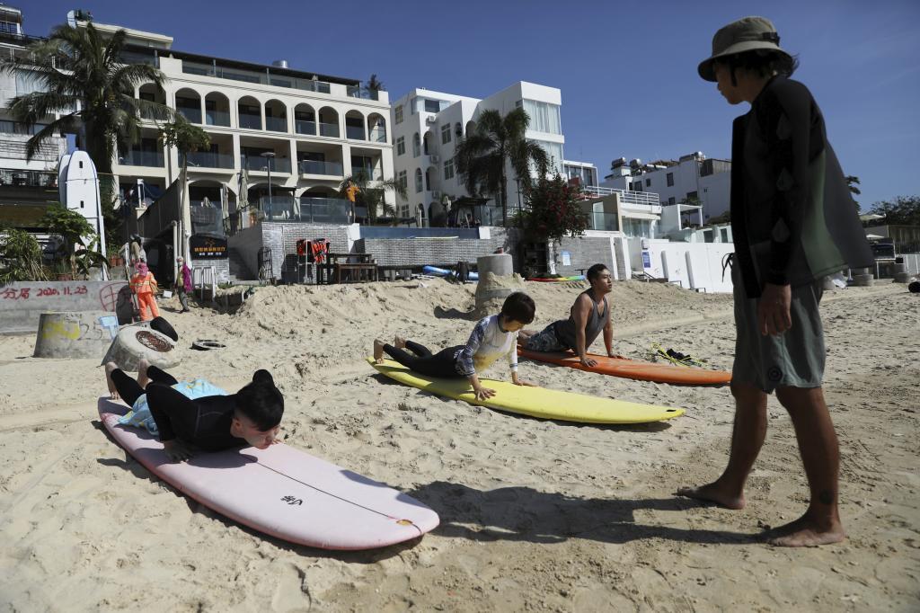Varios jóvenes reciben clases de suf en la playa de Sanya.