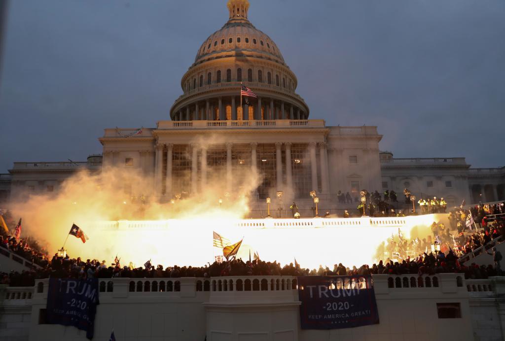 El Capitolio lleno de manifestantes e iluminado por la munición de la Policía que trata de desalojarlo.