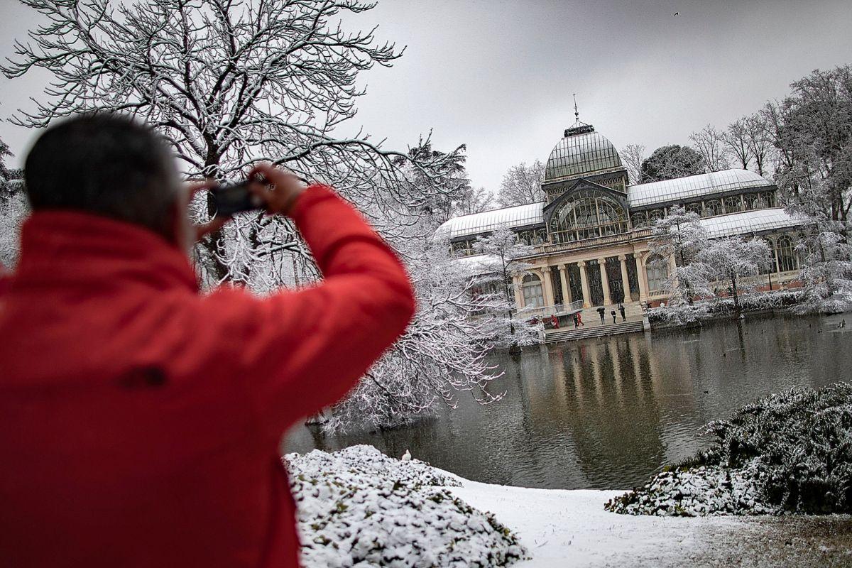 Un hombre, ayer, fotografiando con su teléfono móvil el Palacio de Cristal del Parque de El Retiro tras la nevada caída a partir del mediodía en la capital.