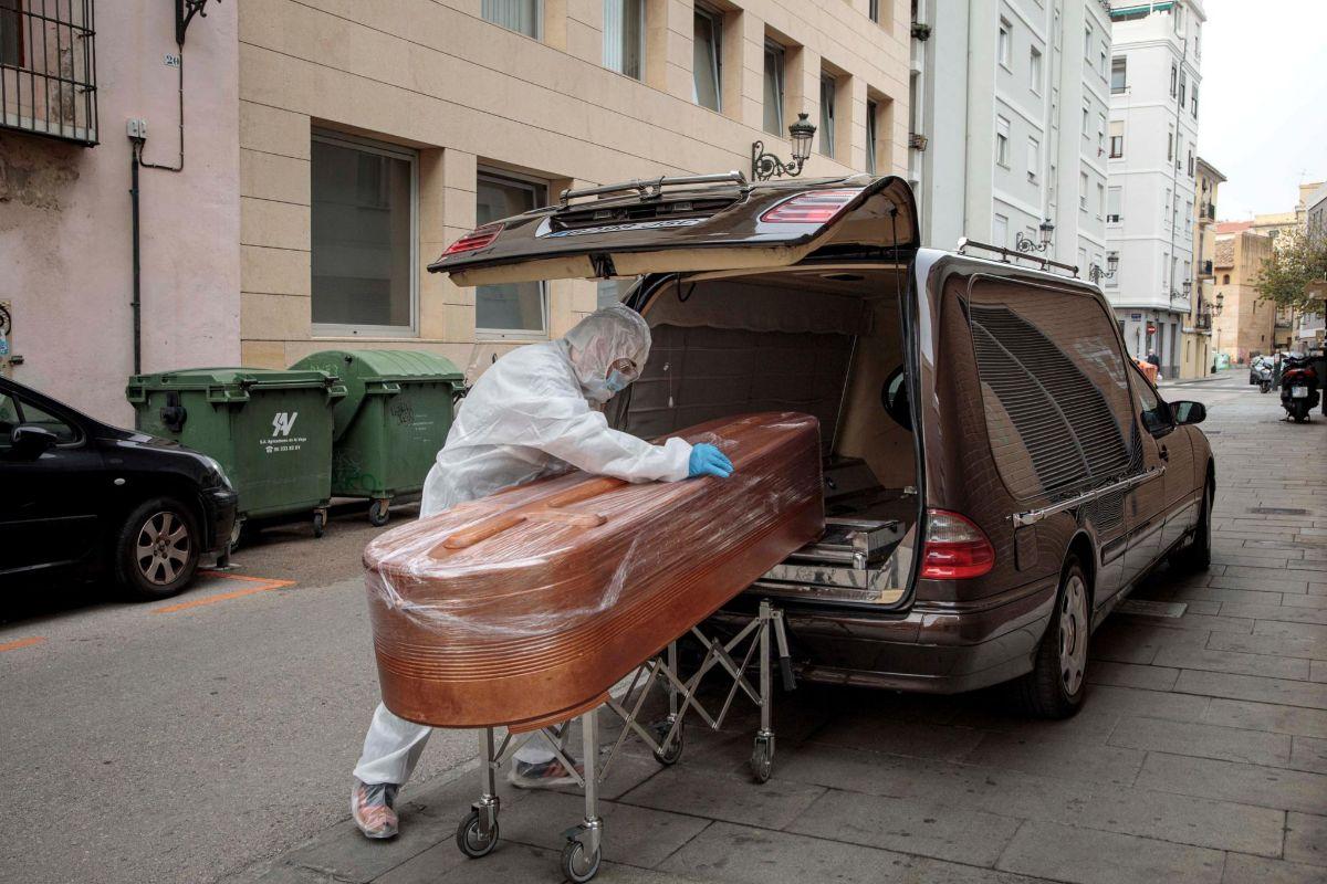 Un operario de una funeraria recoge un féretro en una residencia.
