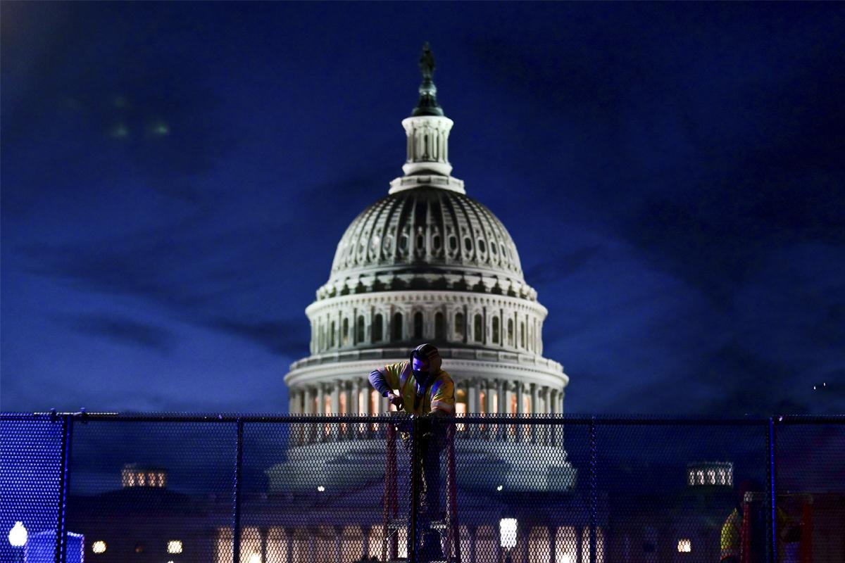 Trabajadores instalan verjas de seguridad en el Capitolio.