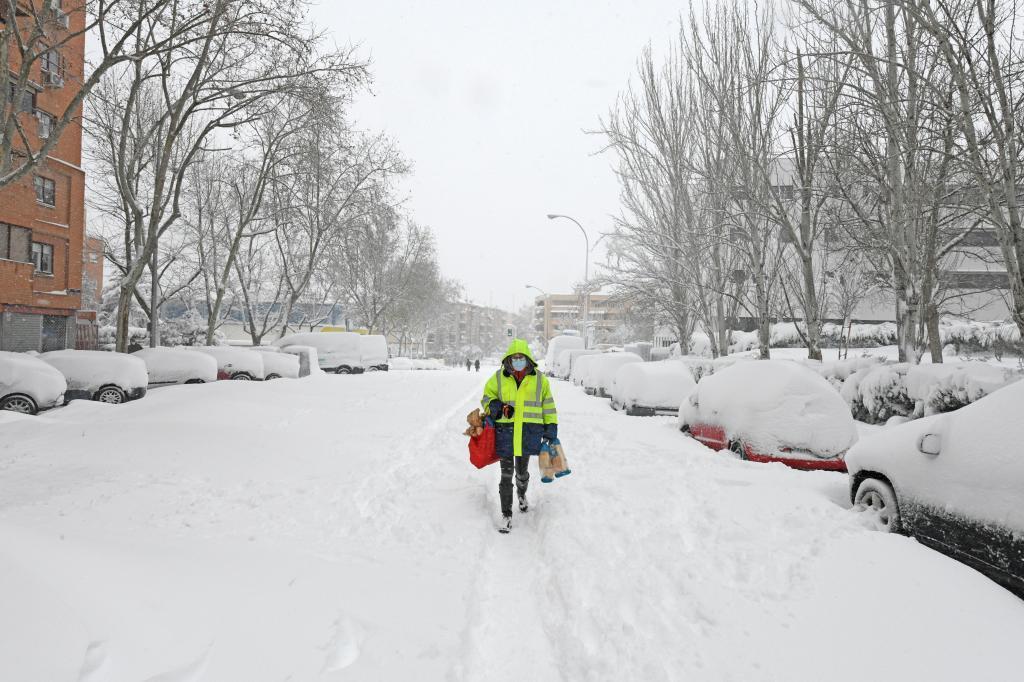 Una vecina de Madrid carga con bolsas de la compra en plena calle nevada.