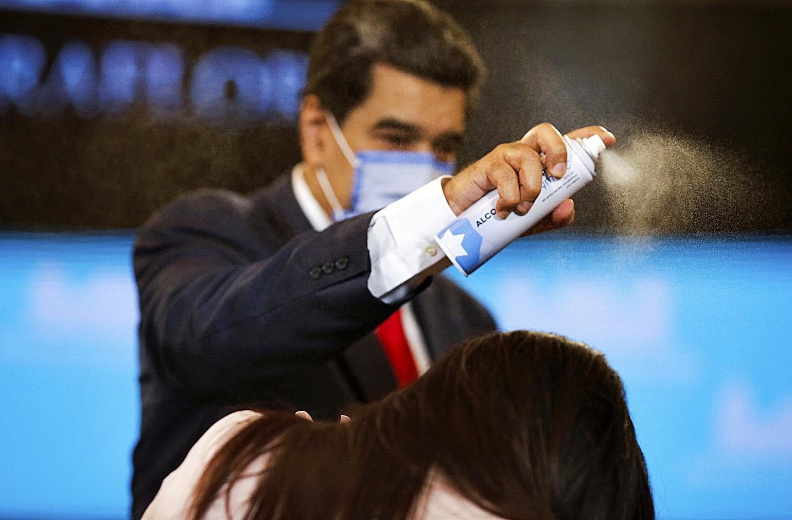 Maduro rocía a una periodista con espray desinfectante.