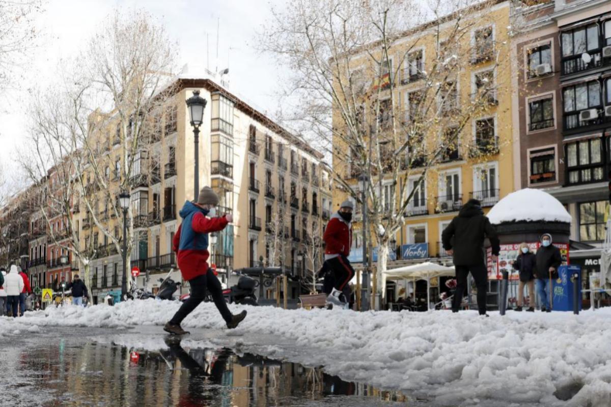 Varias personas disfrutan de la nieve en el centro de Madrid.