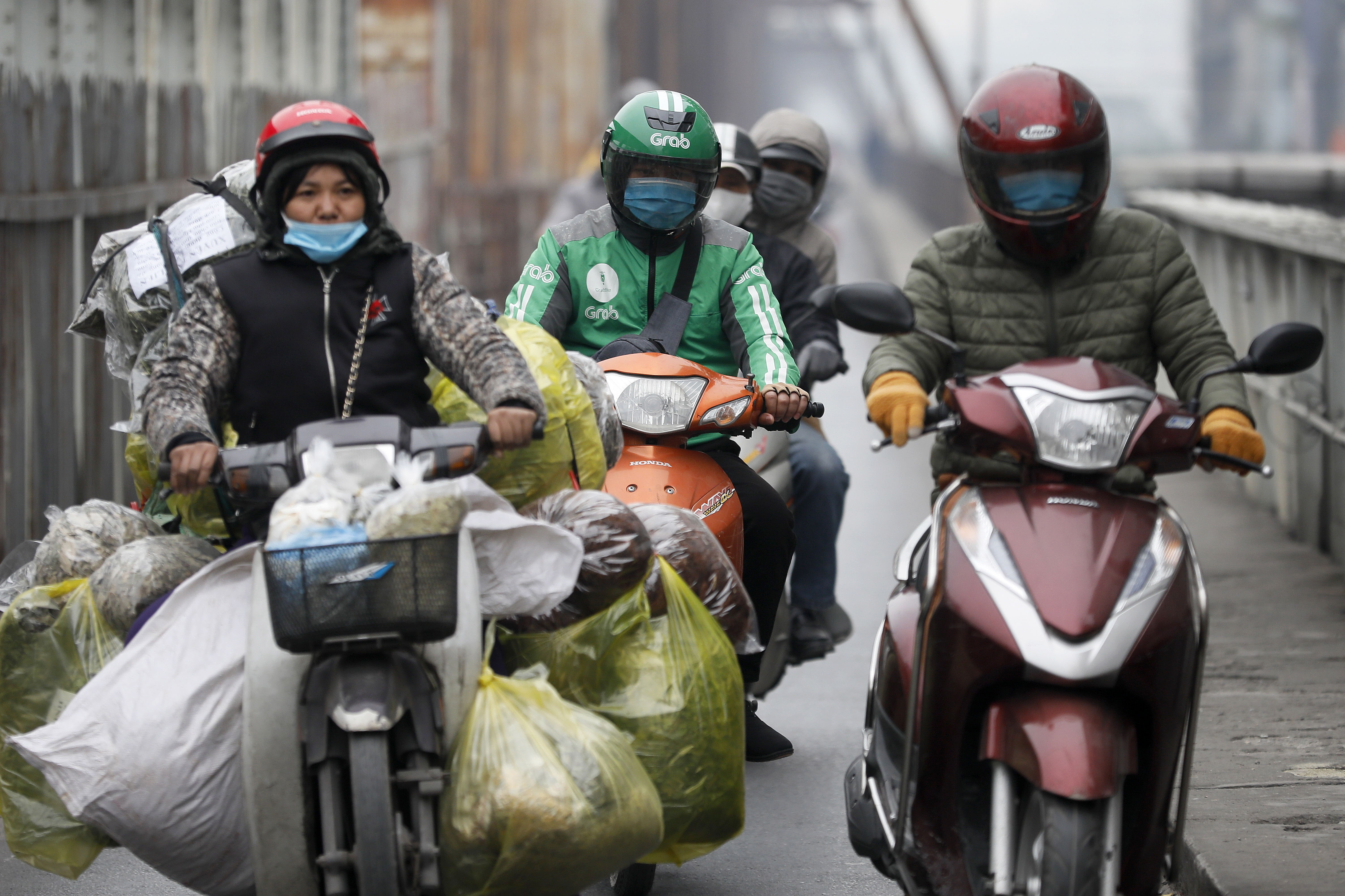 Motoristas con mascarilla en Hanoi.
