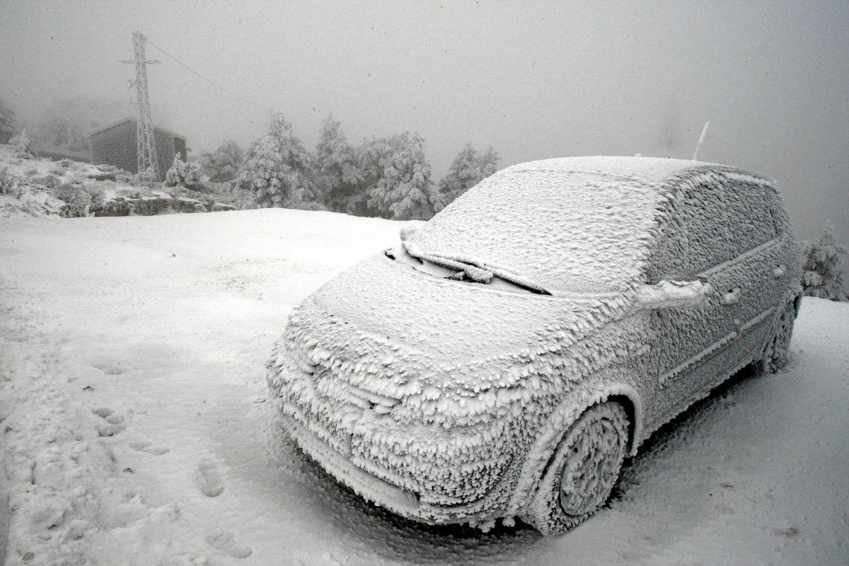 Un coche completamente cubierto de hielo en Navacerrada