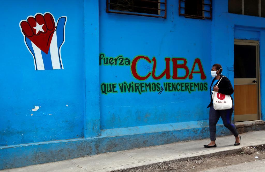 A woman walks in front of a graffiti with a revolutionary slogan today, in Havana.