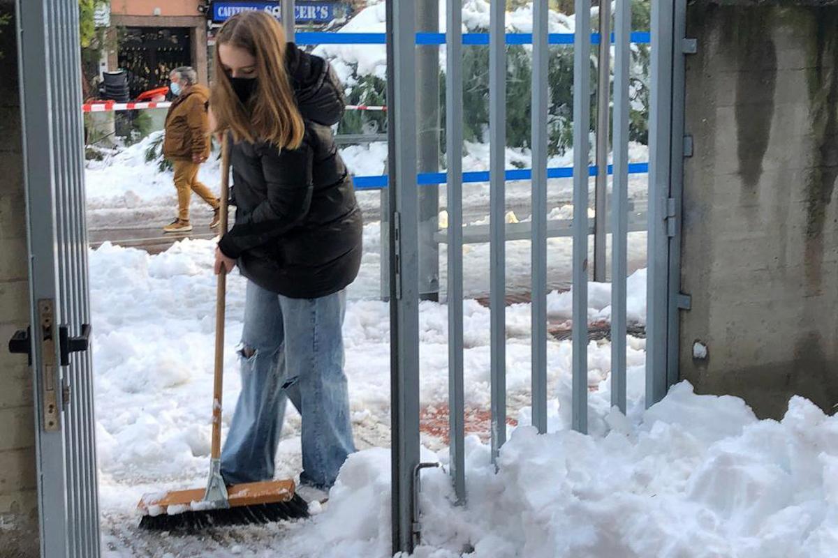 La alumna de 1º de la ESO Victoria Greber limpia de nieve el colegio Santo Ángel de la Guarda de Madrid.