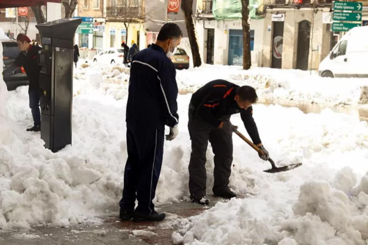 Dos ciudadanos retiran la nieve con una pala en Madrid.