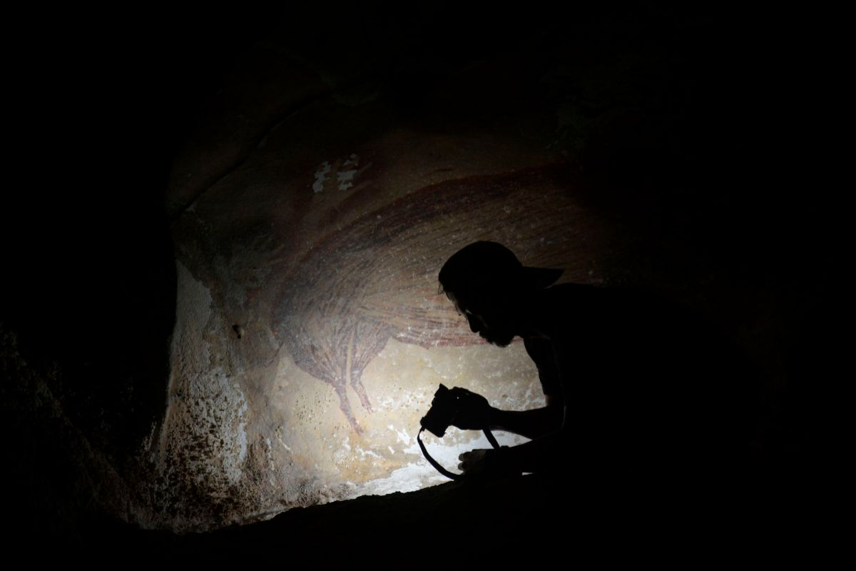 Un arqueólogo, junto a la pintura hallada en Indonesia.