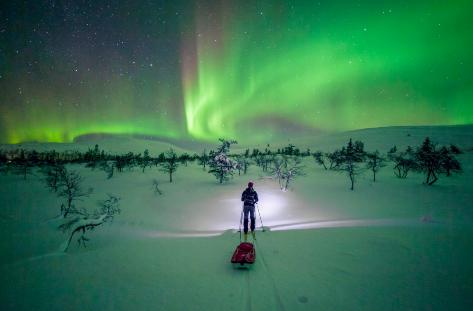 Un esquiador en medio de la nieve contempla una aurora boreal.