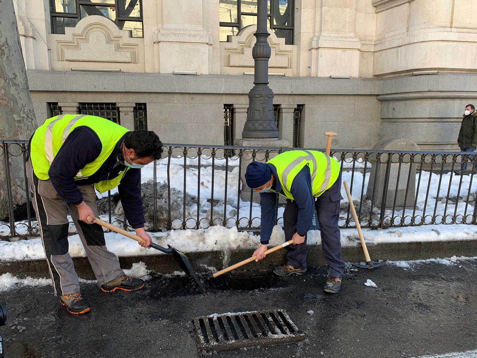 Dos operarios trabajan sobre el alcantarillado de Madrid.