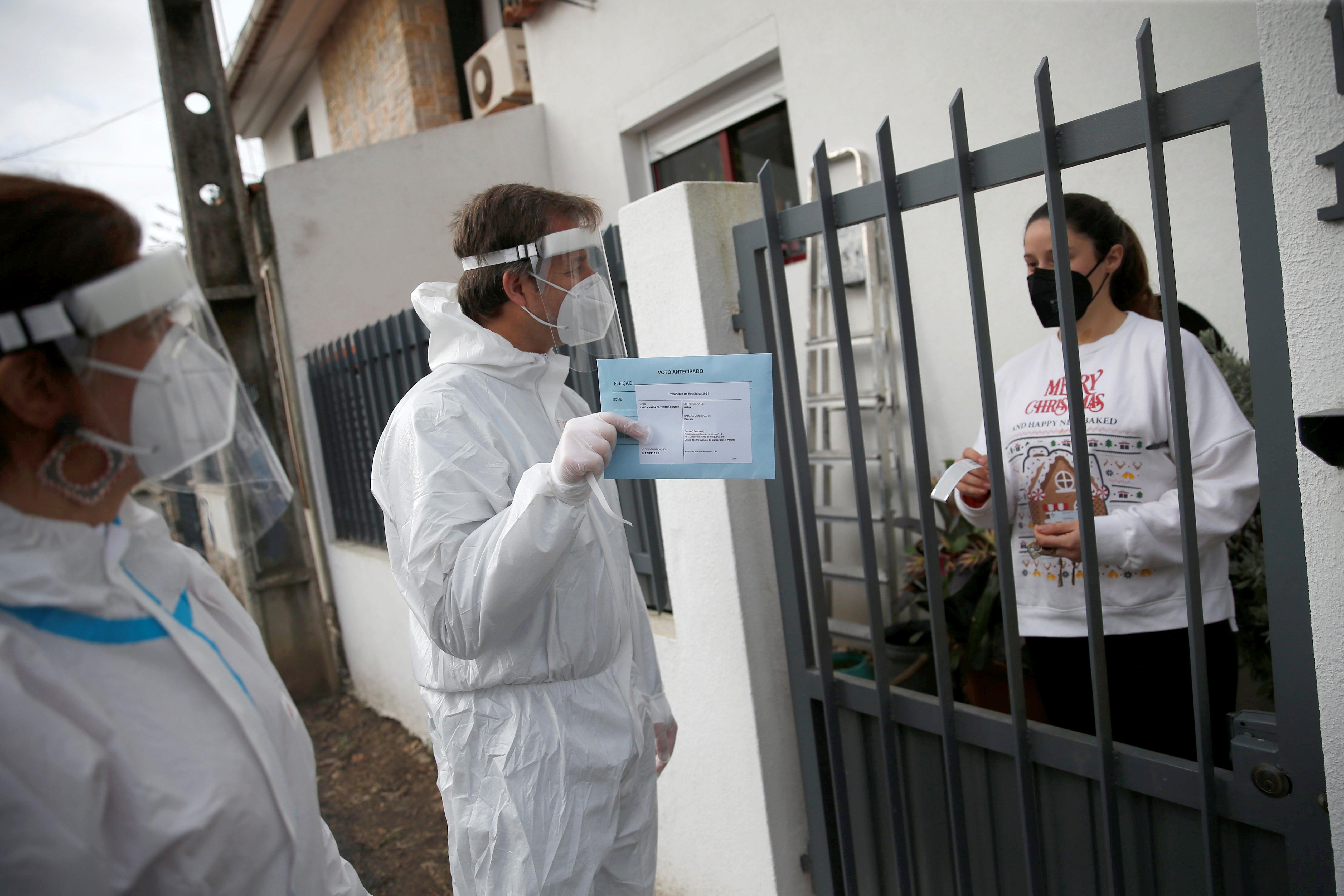 Trabajadores municipales recogen una papeleta para las elecciones del domingo de una votante en aislamiento, en Carcavelos.