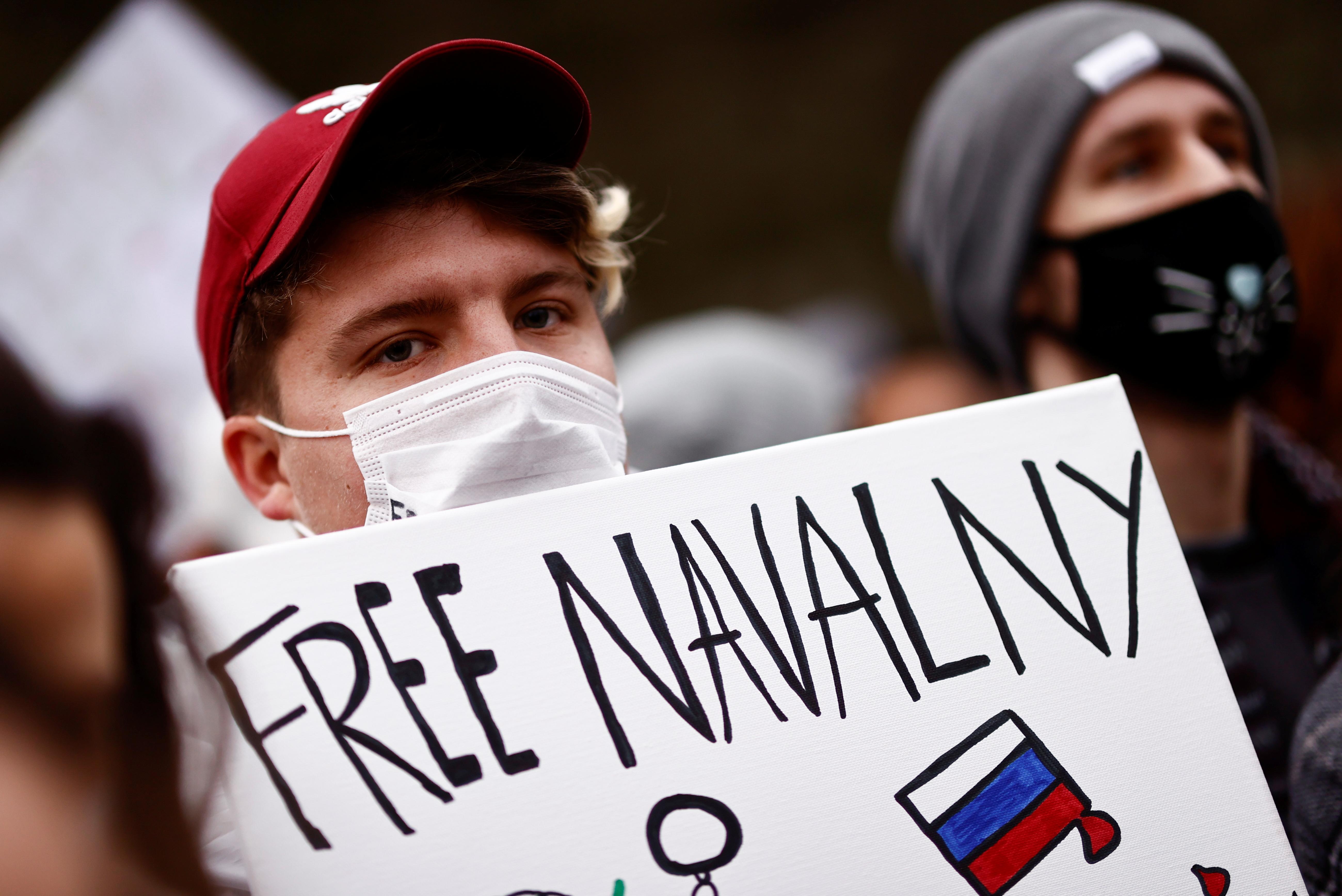 یک جوان روسی بنر بلند می کند و خواستار آزادی ناوالنی است.