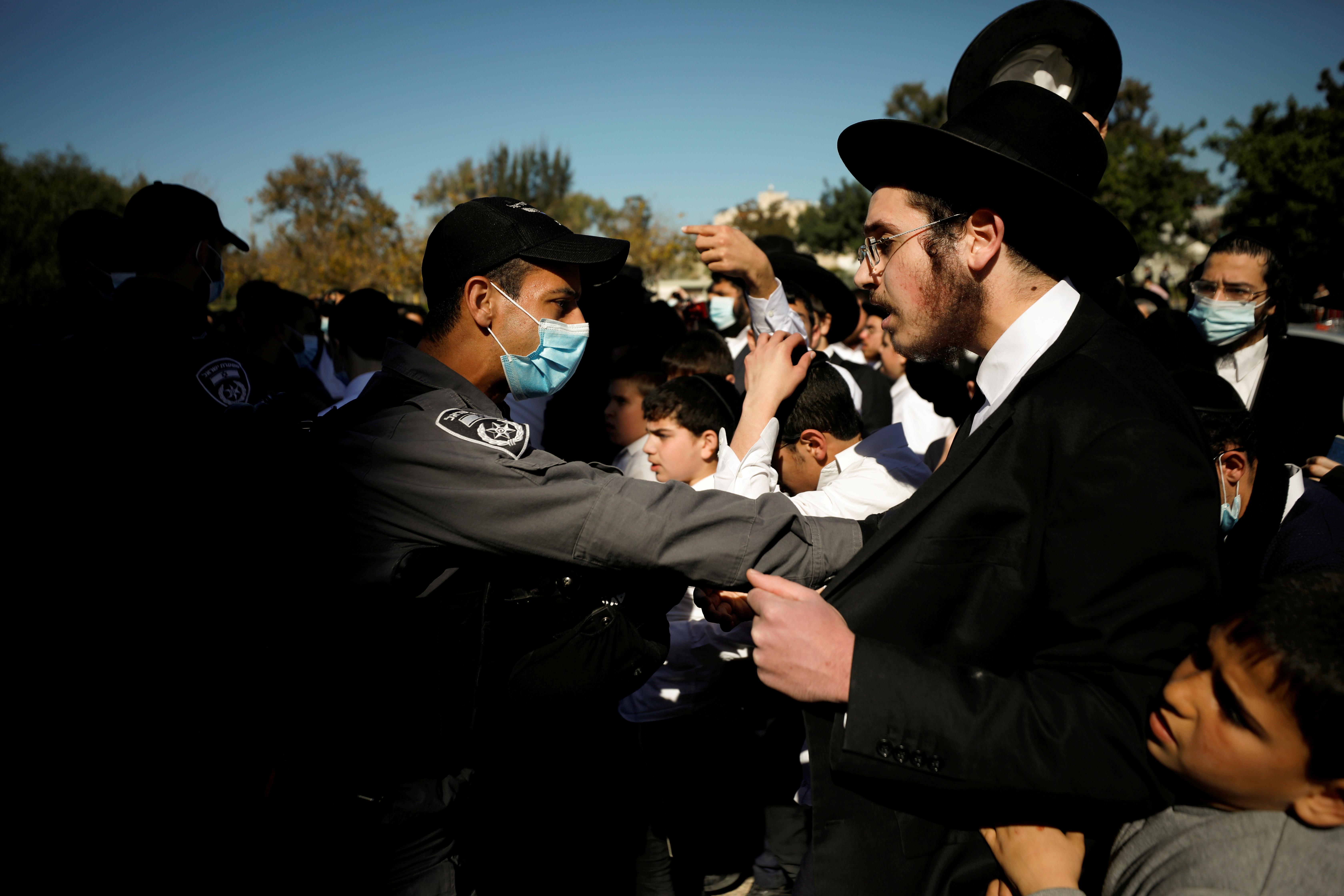 Un policía aparta a un ultraortodoxo durante una protesta.