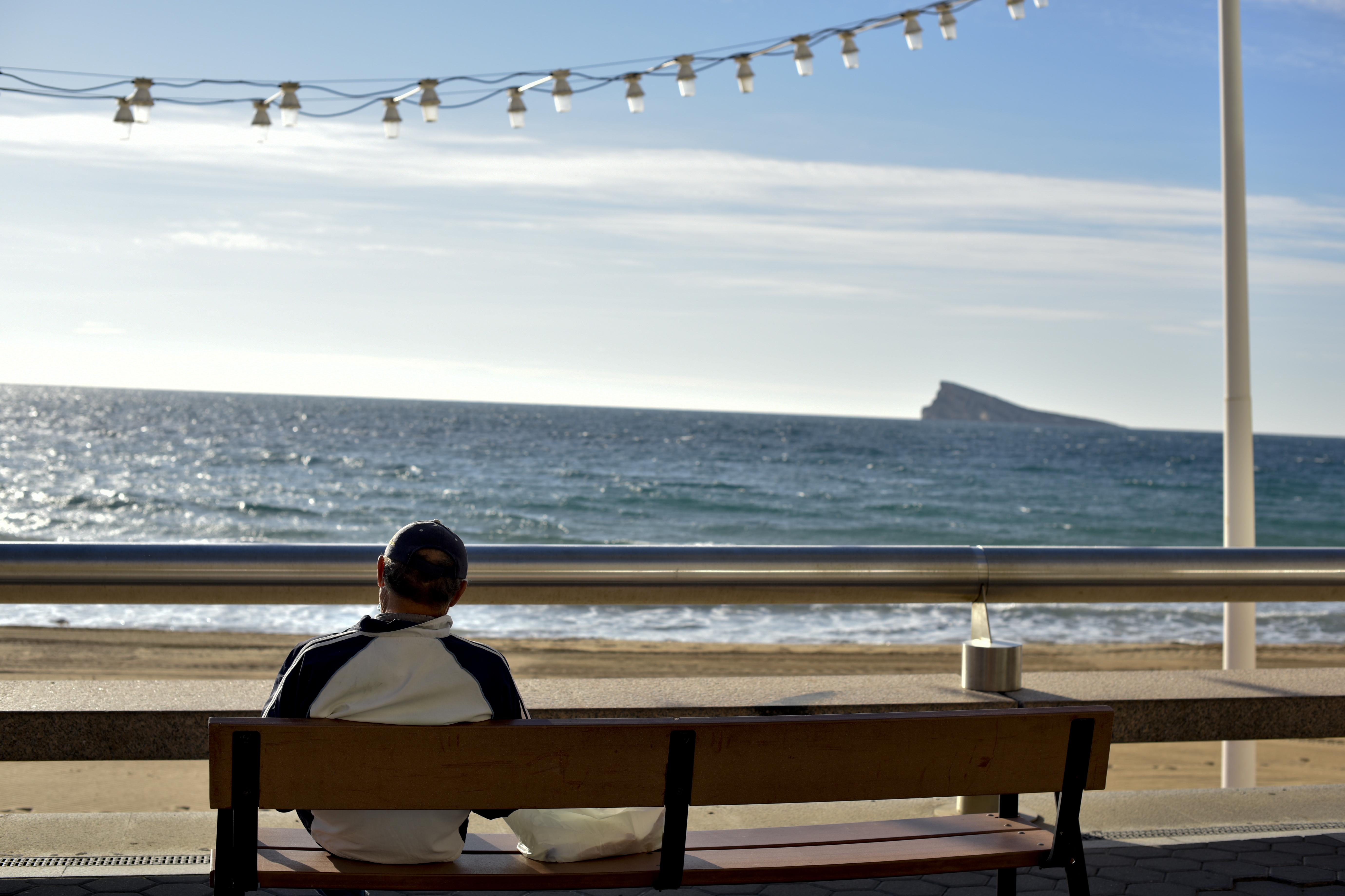 Un jubilado descansa ante la playa de Poniente en Benidorm.