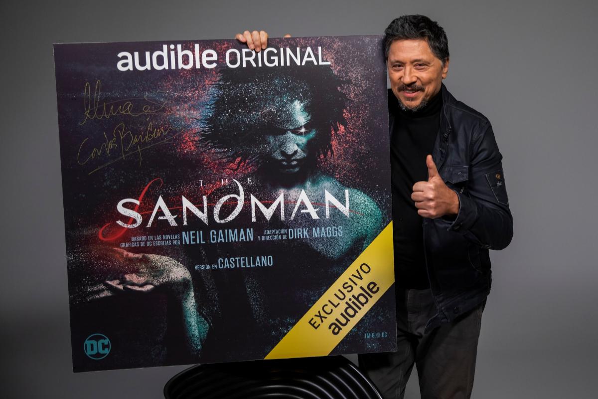 Bardem sostiene el póster de la producción de Audible basada en la obra de Neil Gaiman.