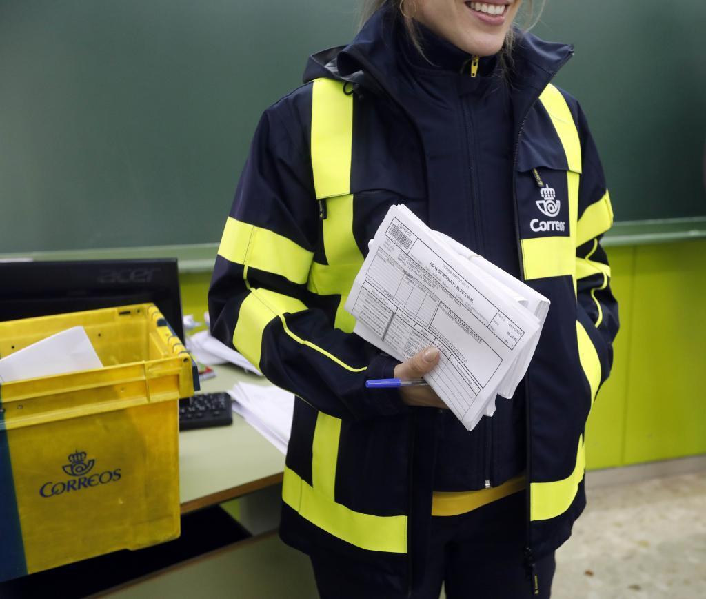 Una cartero lleva el voto por correo