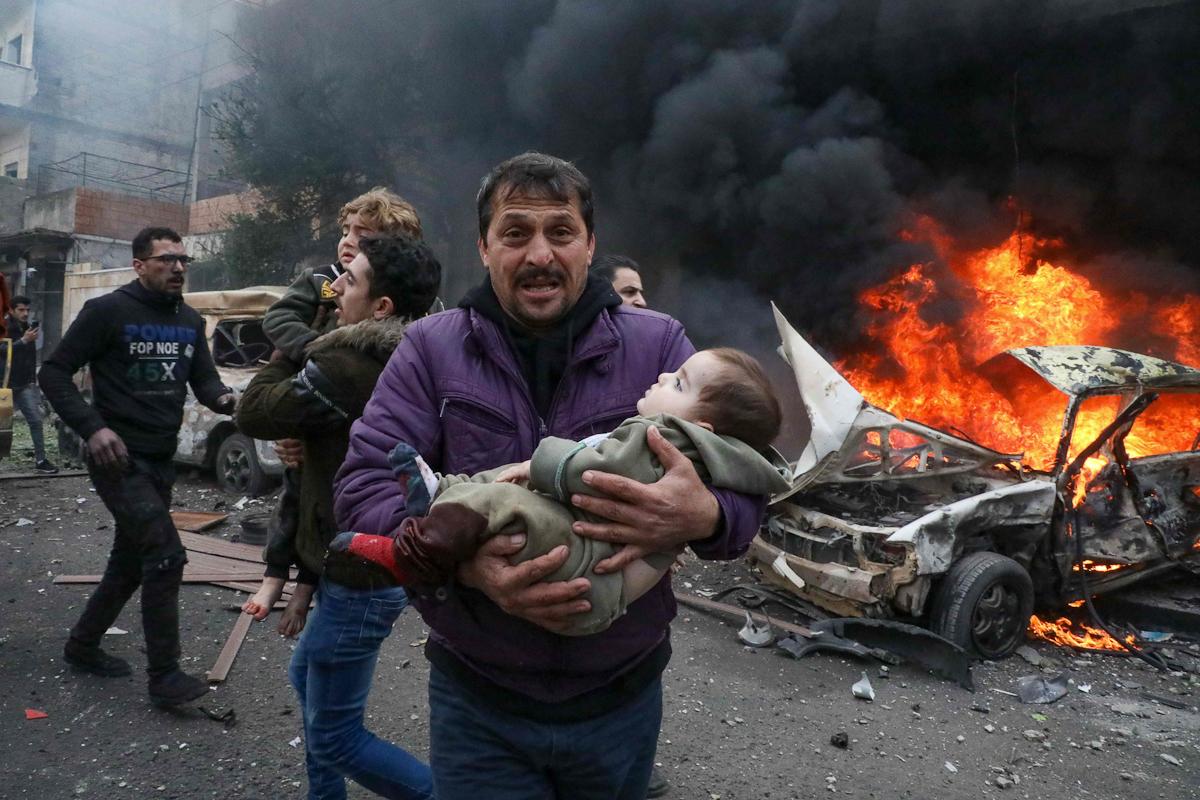 Un hombre sostiene a una niña herida, en Azaz (Alepo).