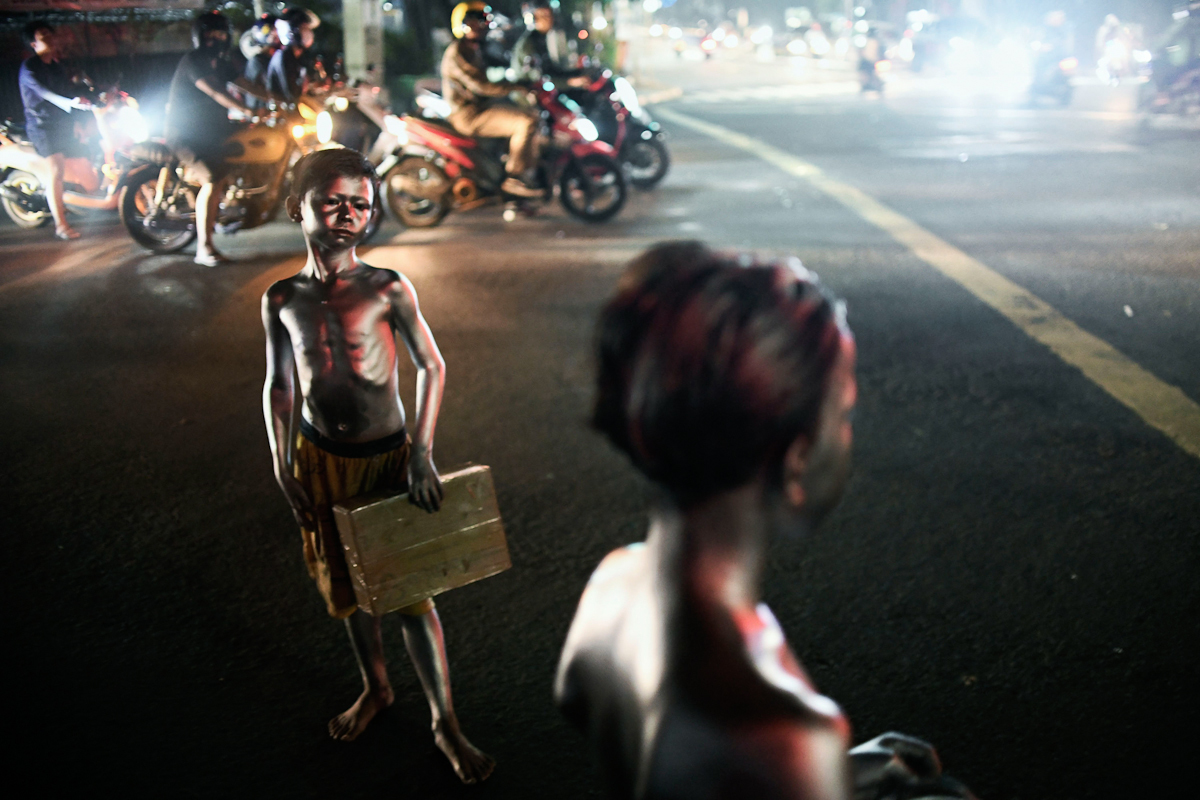 Un niño posa pintado de pintura plateada, en Yakarta.