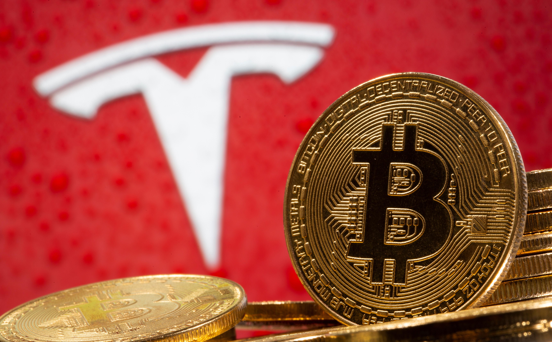 Representación de la moneda virtual bitcoin junto al logotipo de Tesla.