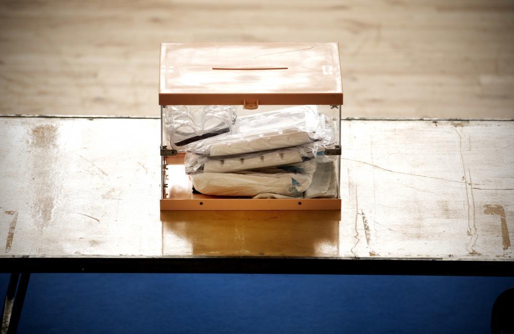 Urna para las elecciones con trajes EPI dentro