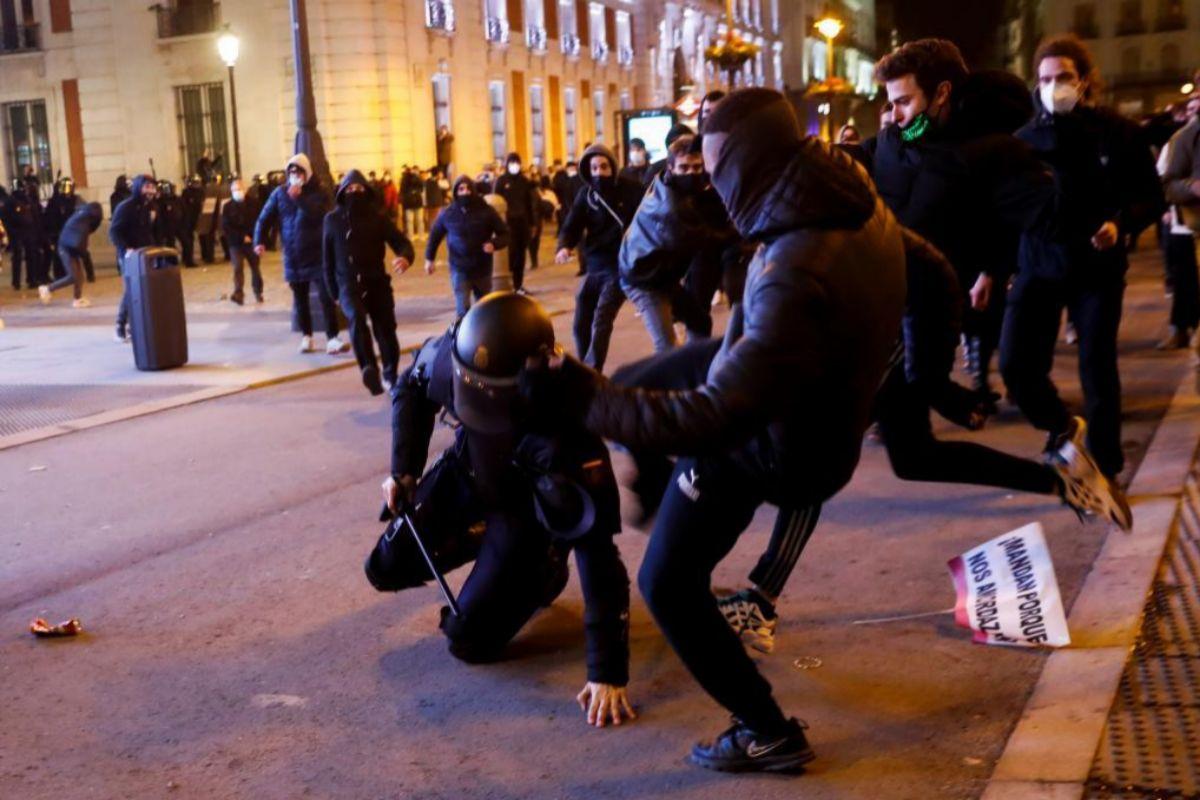 Varios manifestantes acosan a un policía en las protestas de esta noche en Madrid.