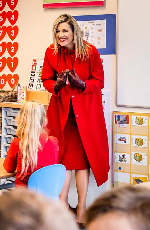La reina de Holanda con look rojo y accesorios burdeos.
