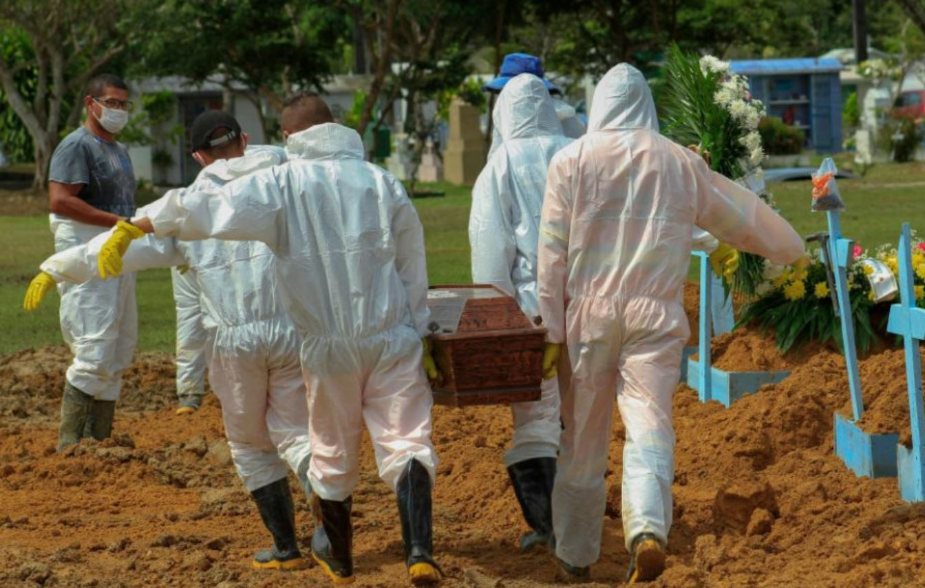 Trabajadores de una funeraria llevan un ataúd para enterrar en Manaos, Brasil.