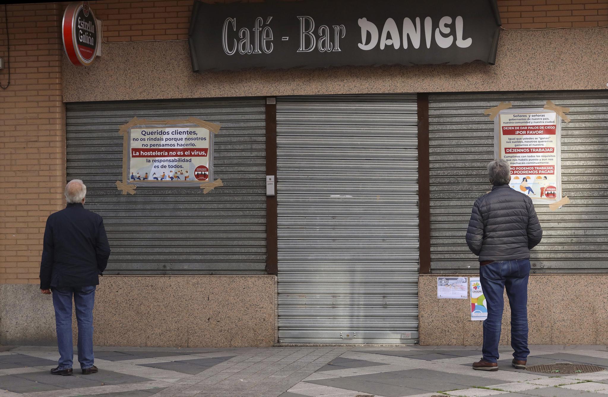 Vecinos leen los carteles de protesta colocados por un hostelero a las puertas de su negocio cerrado en Salamanca.
