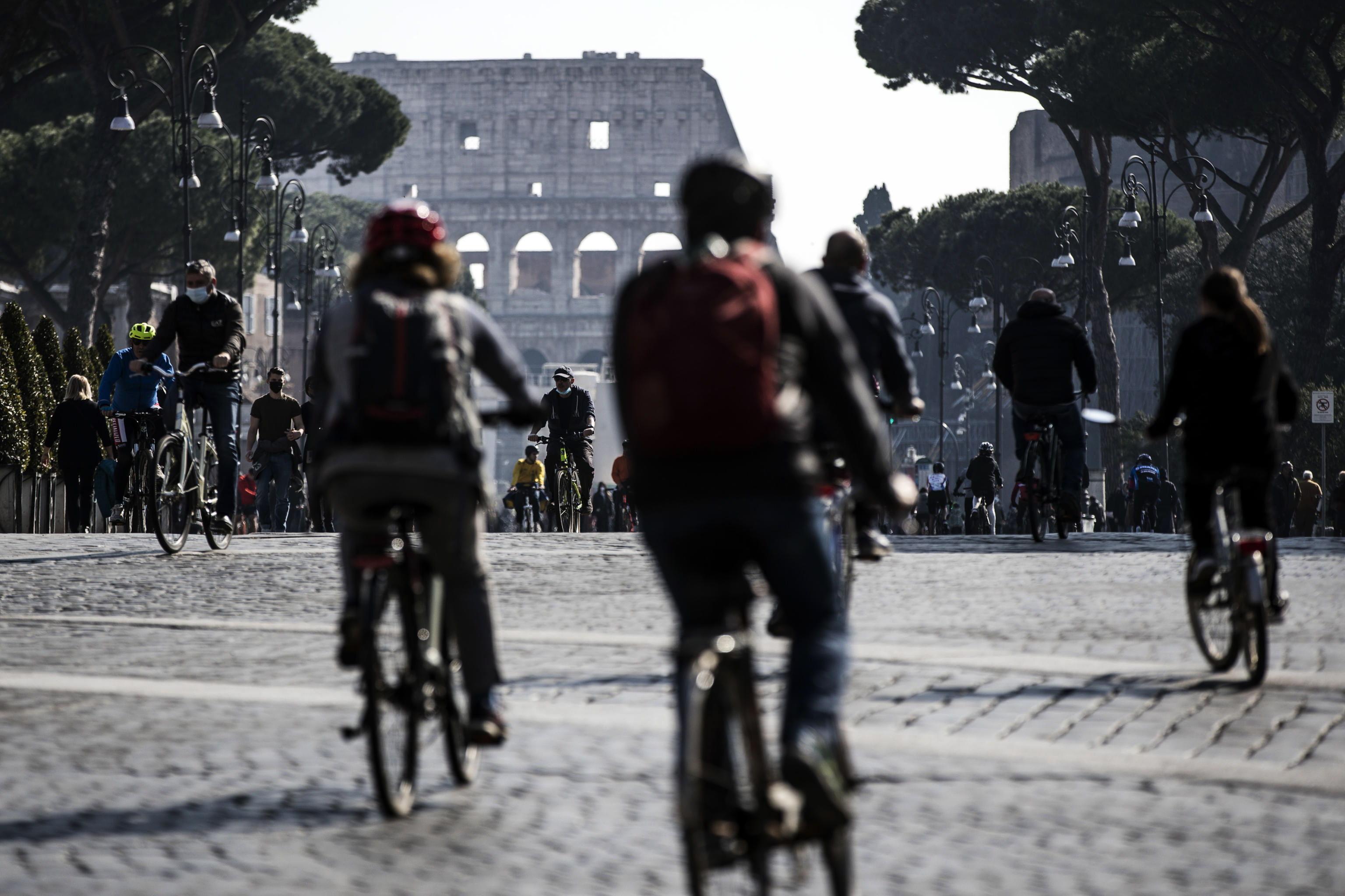 Varias personas montando en bici, con el Coliseo de fondo, en Roma.