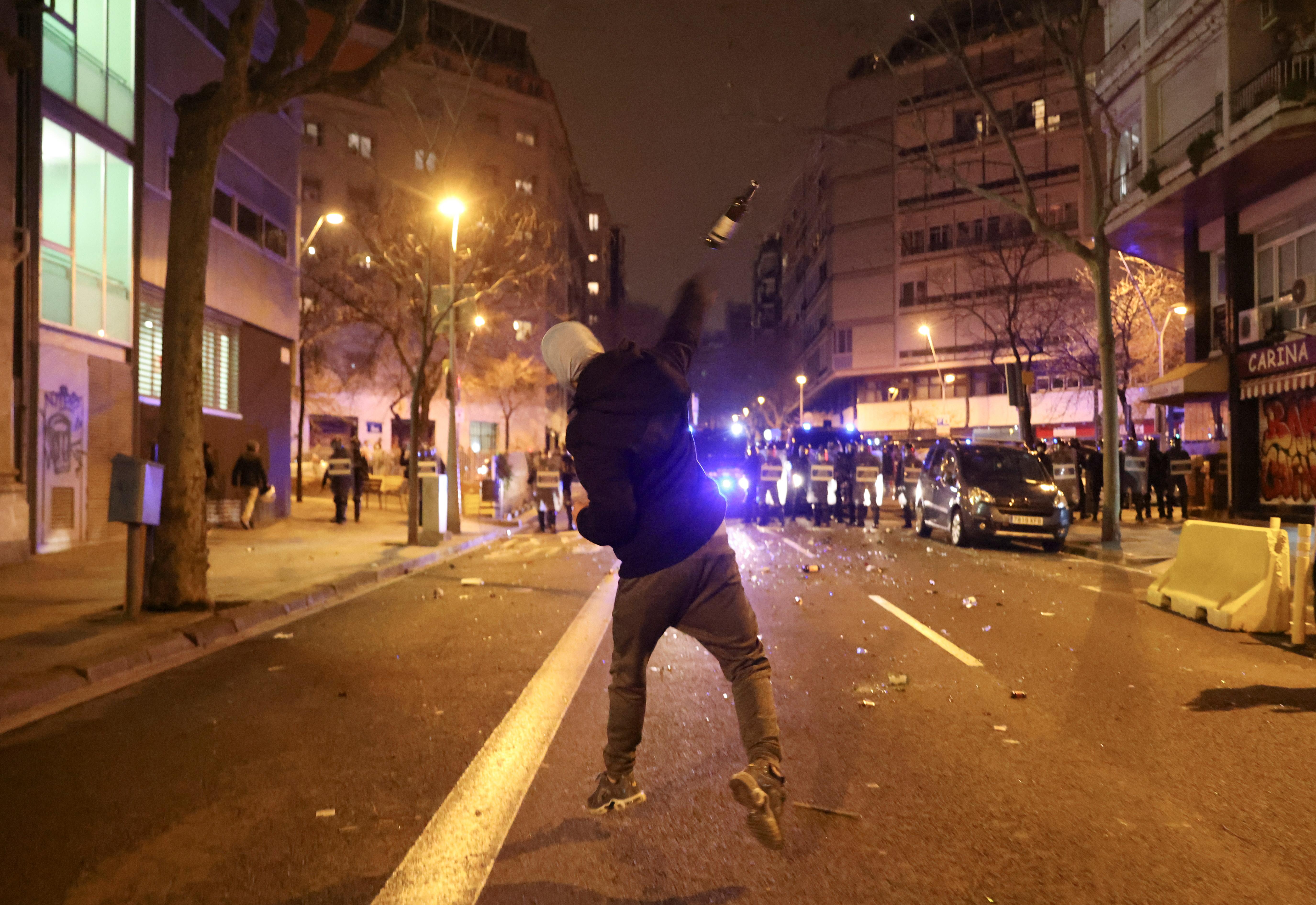 Un manifestante tira una botella a la policía.