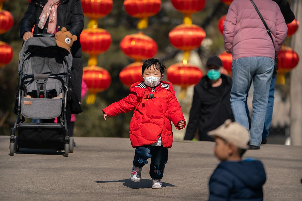 Una niña con mascarilla en un parque de Pekín.