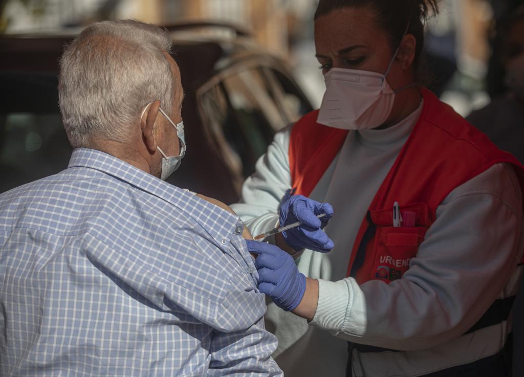 Un sanitario vacuna a un anciano en Sevilla