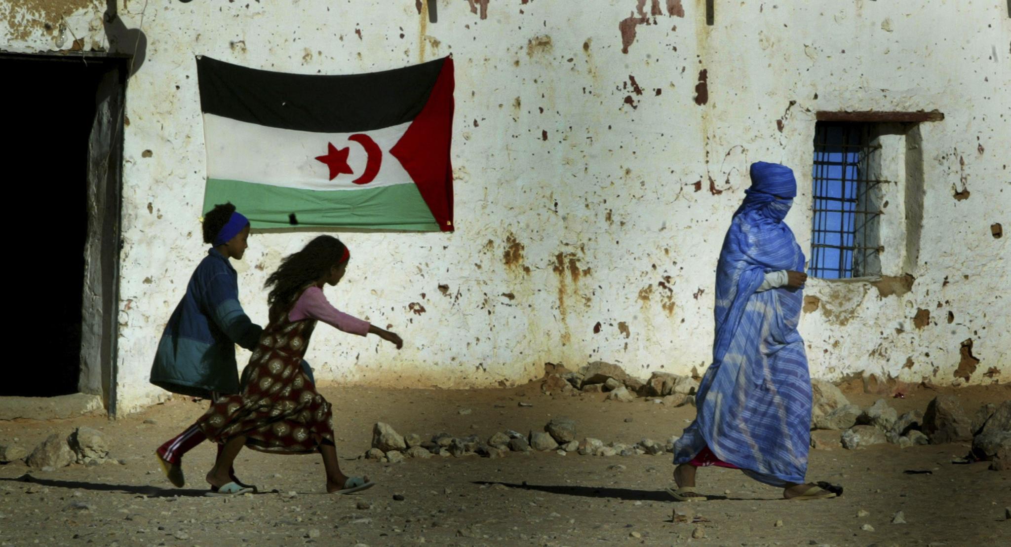 Una mujer junto a un muro con una bandera saharaui, cerca de Tinduf.