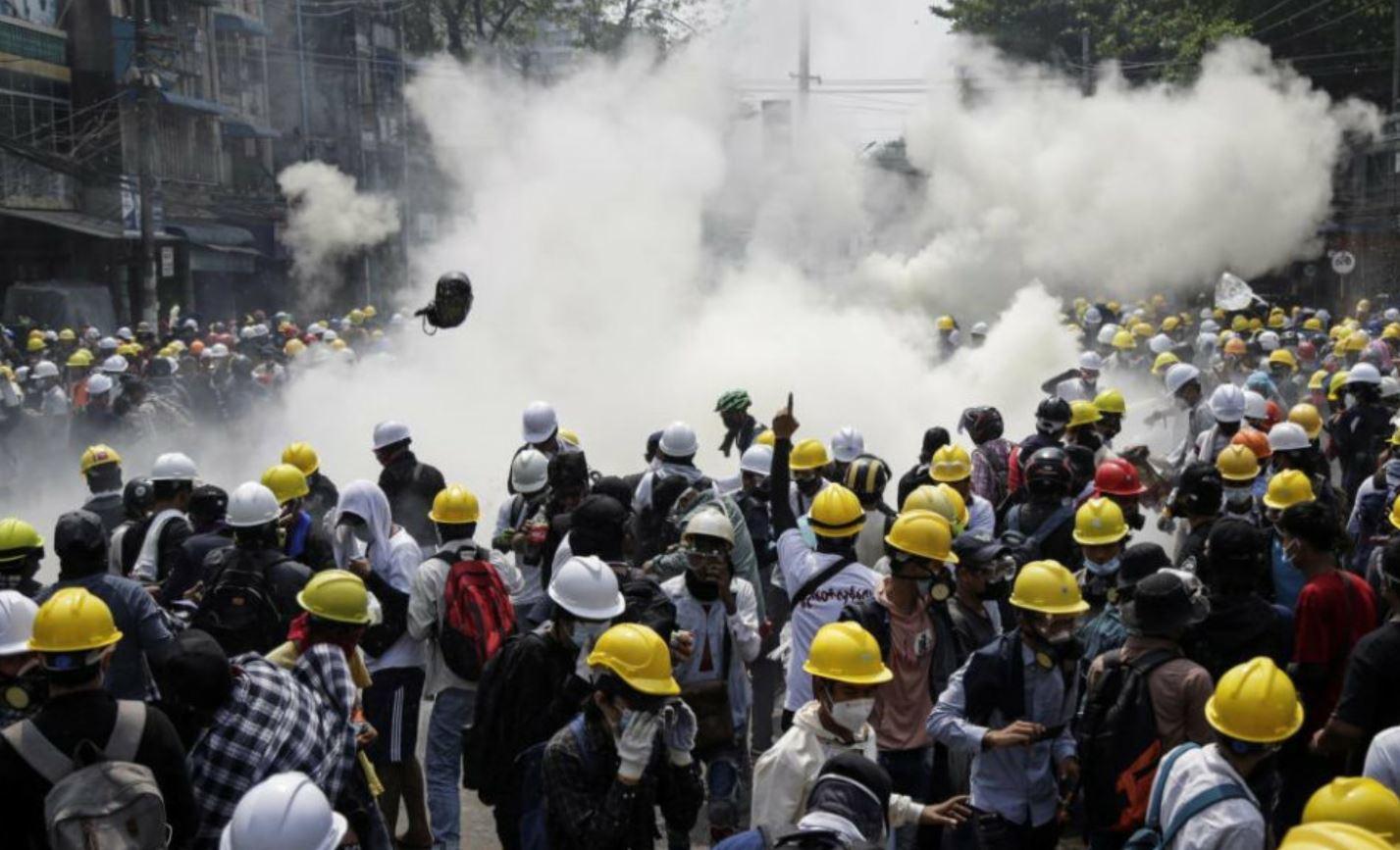 Los manifestantes huyen de los gases lacrimógenos lanzados por la policía durante una manifestación en contra del golpe de estado en las calles de Rangún.