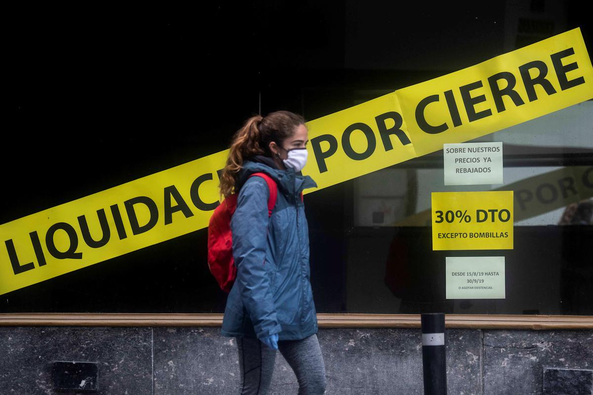 Un mujer pasa frente a un escaparate de una tienda en liquidación en Córdoba.