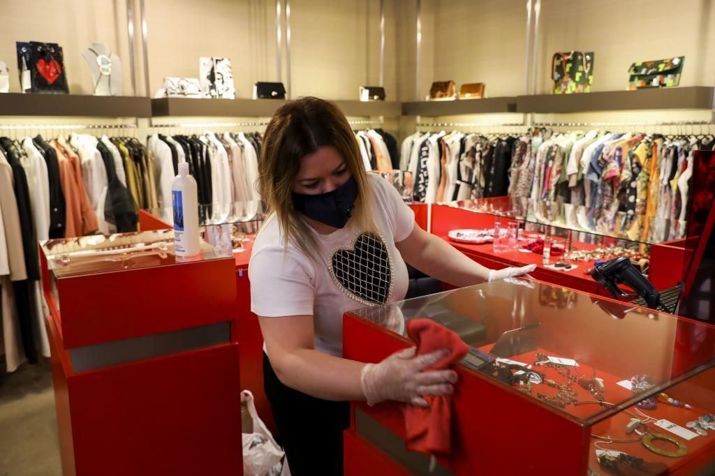 Una dependienta prepara la tienda antes de abrir