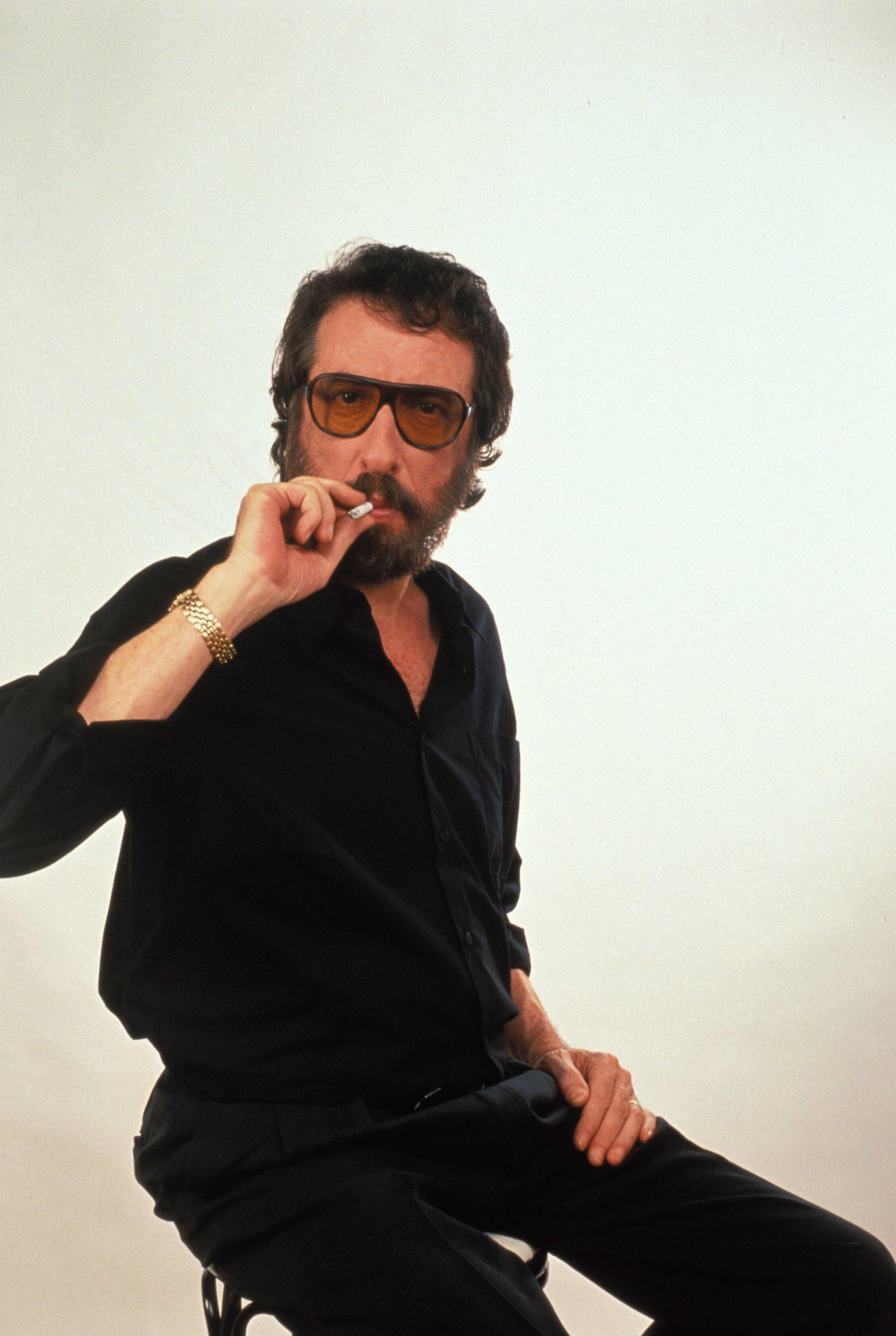 El humorista Eugenio, con su característica estética de ropa negra, gafas ahumadas y fumando.