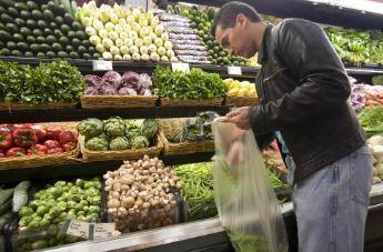 Un hombre compra frutas y verduras en un supermercado.