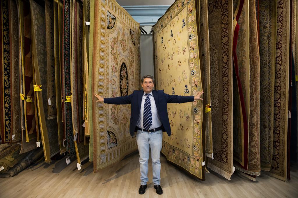 Delfín Muñoz, entre sus alfombras, en la tienda de Madrid.