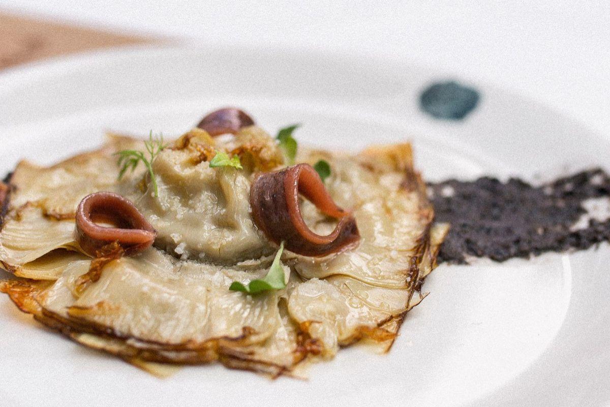 Con anchoas de Santoña, tierra de aceitunas y crema de piparras, en Flores de Alcachofa.