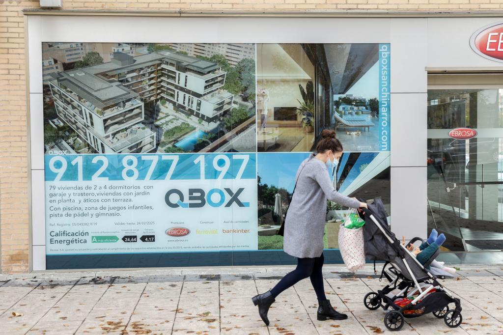 Una mujer con un carrito de bebé pasa ante una agencia inmobiliaria.