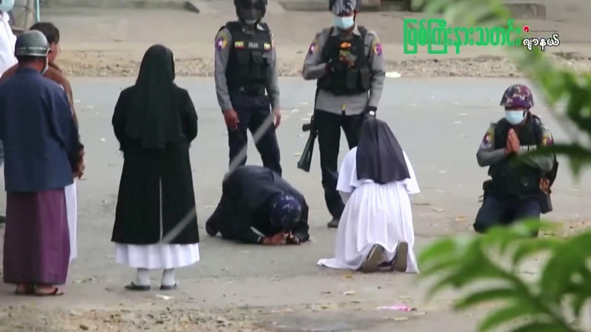 La monja Ann Rose Nu Tawng se arrodilla ante policías birmanos.