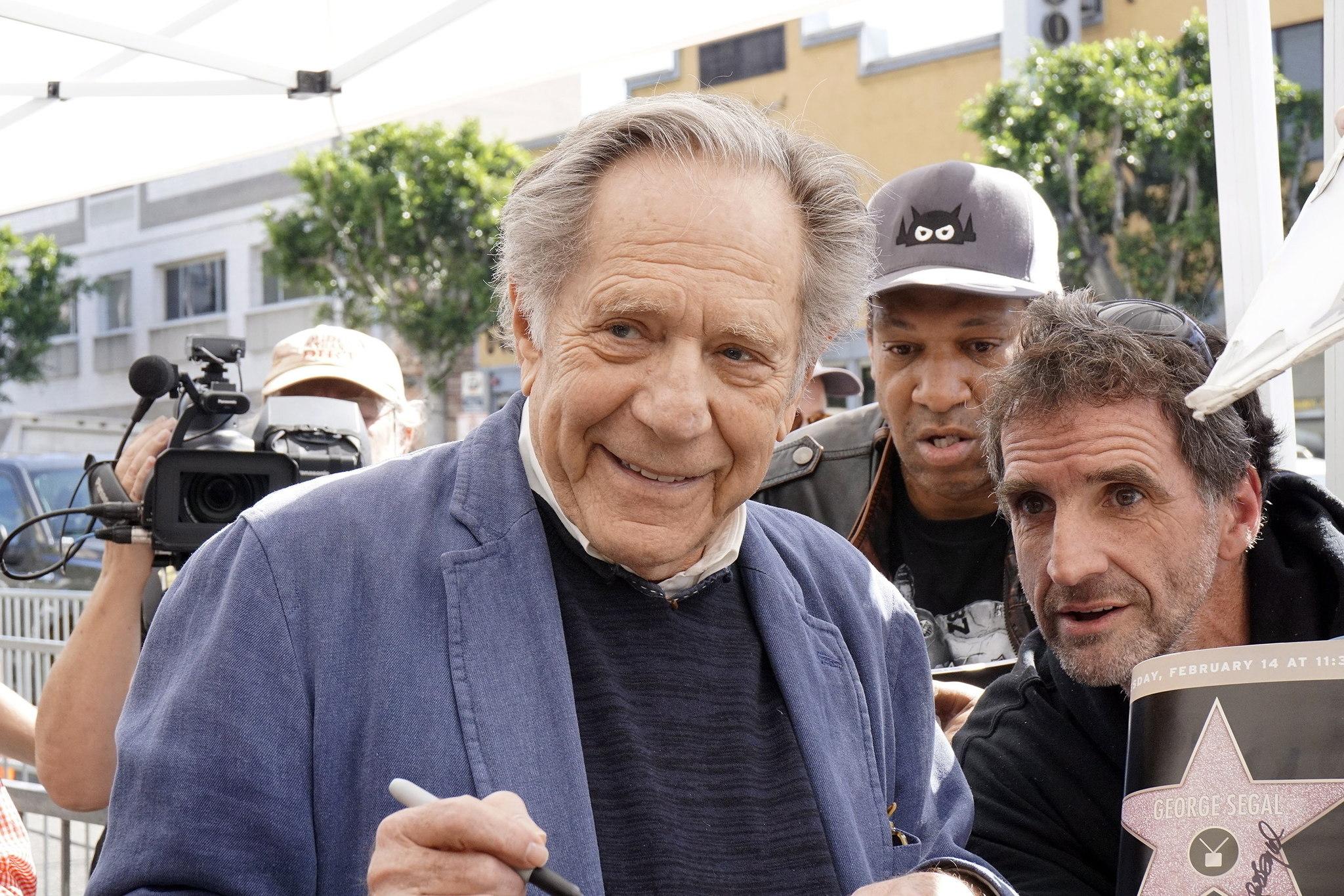 El actor estadounidense George Segal posa con sus fans en el Paseo de la Fama de Hollywood durante la ceremonia de entrega de la estrella del Paseo de la Fama de Hollywood en Hollywood, California, Estados Unidos.