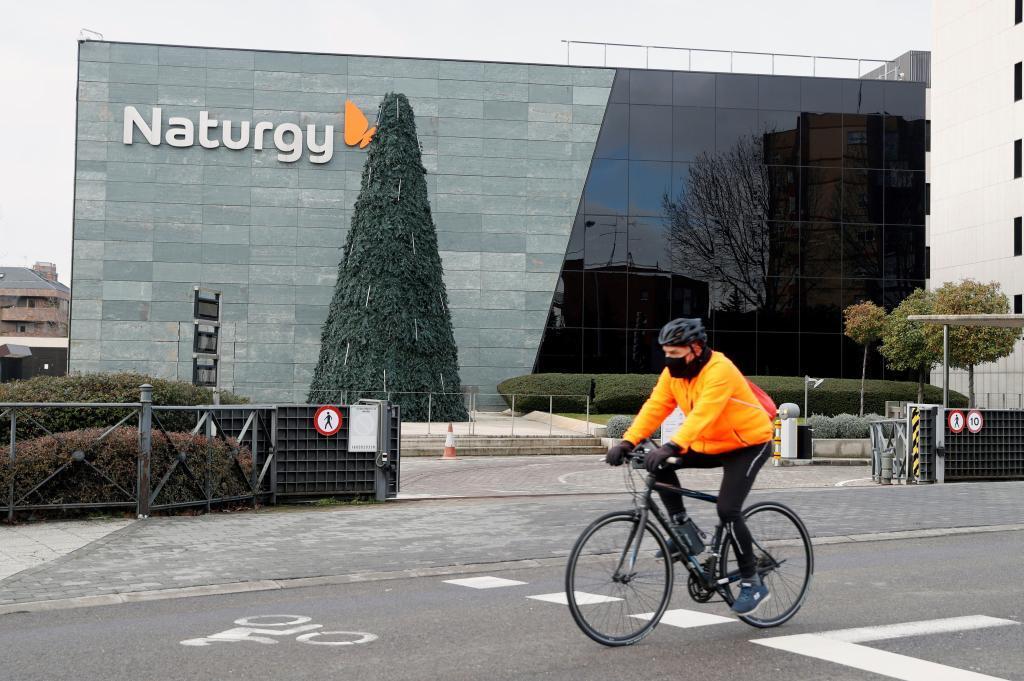 Un ciclista, frente a la sede de Naturgy, en Madrid.