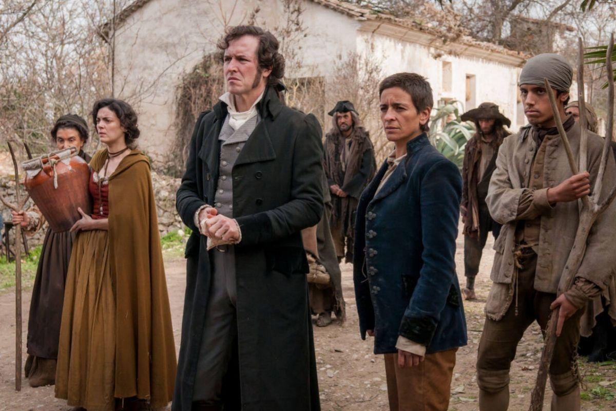 Jorge Suquet (en el centro) es John, un escritor que quiere contar la historia de 'La Llanera' (Bebe).