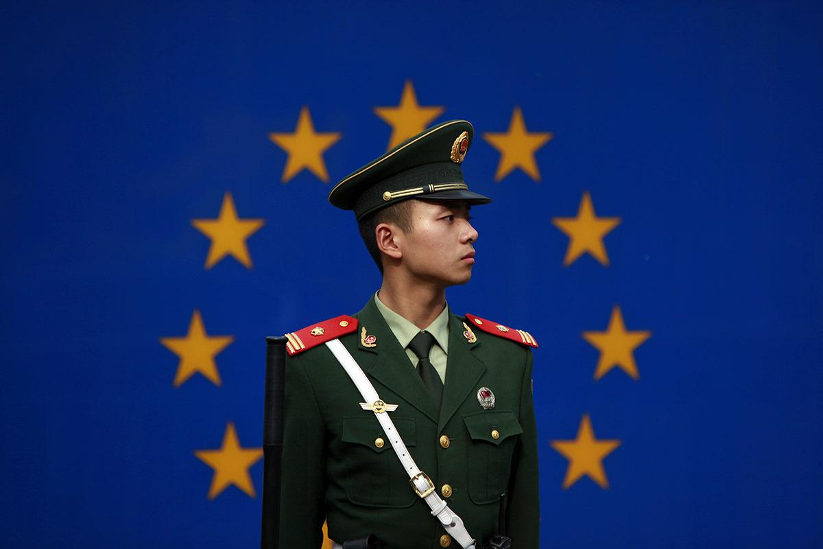 Un militar chino frente a la bandera de la UE en Pekín.