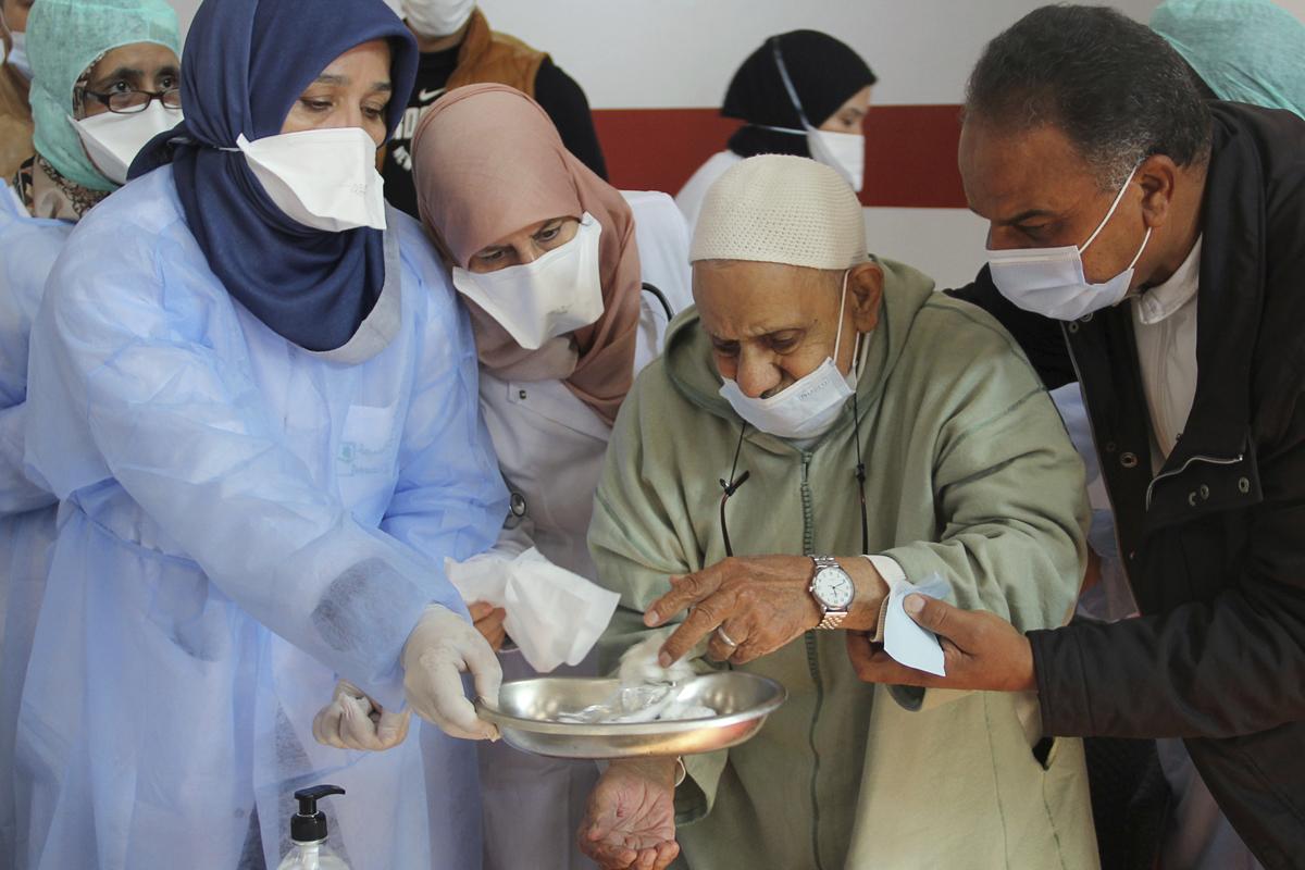 Sanitarios atienden a un anciano recién vacunado en Salé.